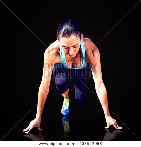 Composite image of sportswoman in the starting block against black background