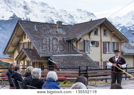 zurich,switzerland:alphorn performance on wooden floor before house near alpes mountains by zhudifeng on Oct 12 2015