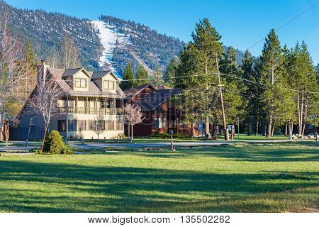 spring landscape of houses on the shore of Lake Tahoe in the background ski