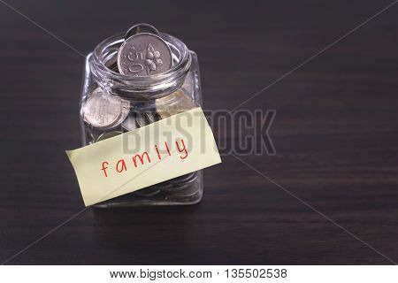 Finacial concept. Money in the glass on wooden table with family word and copy space area.
