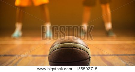 Close up on basketball putting on the floor in front of basketball players on a gym