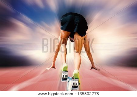 Composite image of sportsman on starting blocks against blurred background