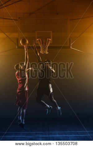 Basketballs player trying to scoring a basket while one trying to block him