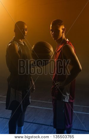 Two basketball player holding a single basketball in a gymnasium