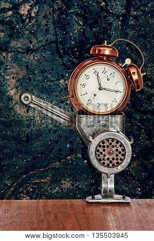 Bronze vintage alarm clock in meat grinder on blue grunge wall background.