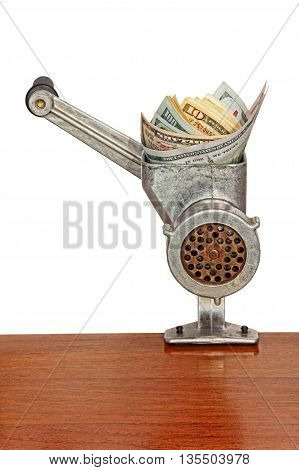 Money concept with dollar banknotes in meat grinder on wooden table and white background.