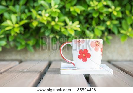 Closeup beautiful cup of coffee on white book on blurred wooden table and green plant in the garden textured background relaxation concept with cute cup and book