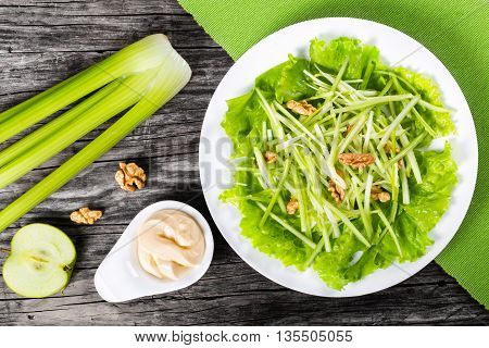 fresh Waldorf Salad with walnuts green apple and celery authentic recipe half of a lemon celery and mayo in a gravy boat on a wood table view from above studio lights