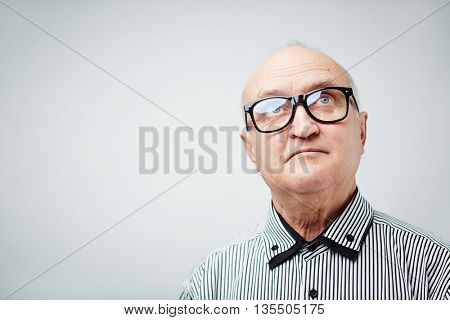 Portrait of senior in glasses looking up