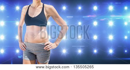 Portrait of sportswoman is posing and smiling against composite image of blue spotlight