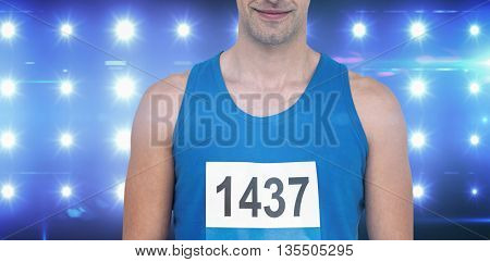 Male athlete standing on white background against composite image of blue spotlight