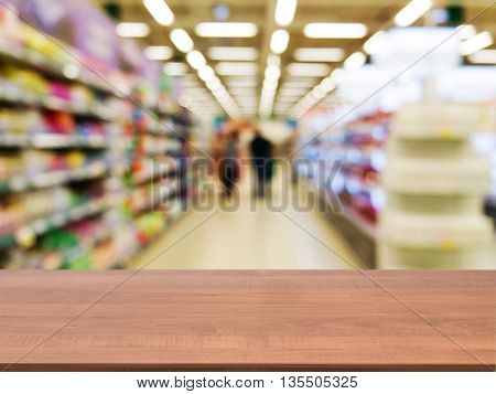 Wooden board empty table in front of blurred background. Perspective dark wood over blur in supermarket - can be used for display or montage your products. Mock up for display of product.