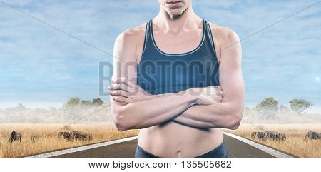 Athlete posing with arms crossed against savannah road landscape