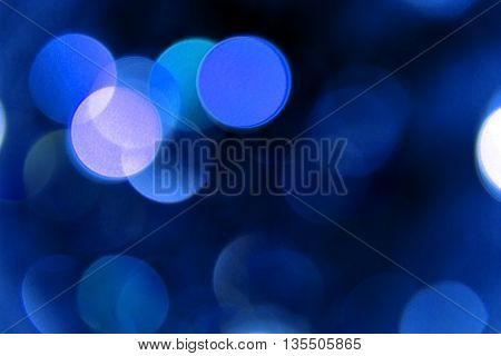 Blurred reflections of the light. Unfocused image of blue light.