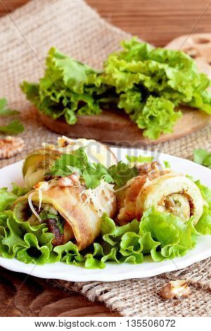 Fried zucchini rolls with cheese, walnuts and herbs. Fried stuffed zucchini rolls on a plate. Fresh lettuce leaves on a wooden board. Healthy and delicious summer appetizer