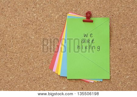 we are hiring on color sticker notes over cork board background