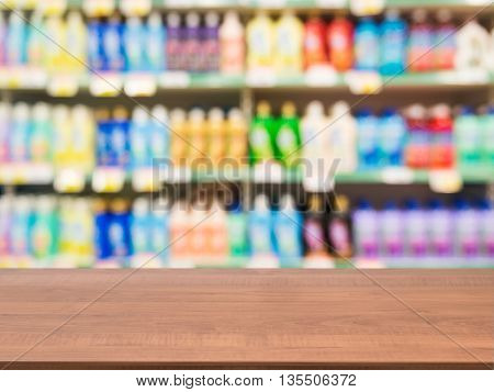 Wooden board empty table in front of blurred background. Perspective dark wood over blur colorful supermarket products on shelves. Mock up for display or montage of product