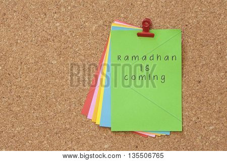 ramadhan is coming on color sticker notes over cork board background