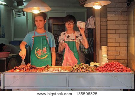 Wuhan, China - June 22, 2015: girl and boy are selling snacks outdoor in Wuhan, China