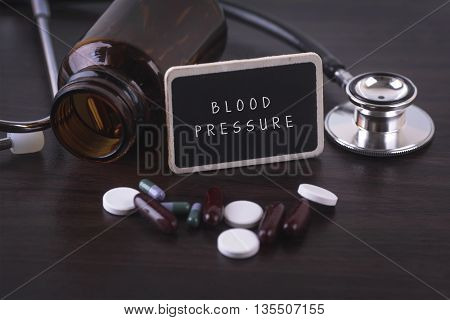 Stethoscope pill bottle Various pills capsules and BLOOD PRESSURE on wooden background with copyspace area.