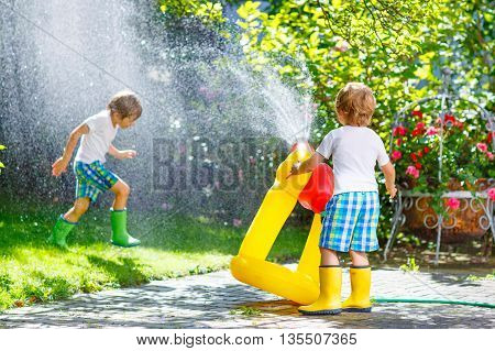 Two little friends, kid boys playing together with a garden hose on hot and sunny summer day. Two siblings having fun outdoors. Funny outdoors leisure wth water for children.
