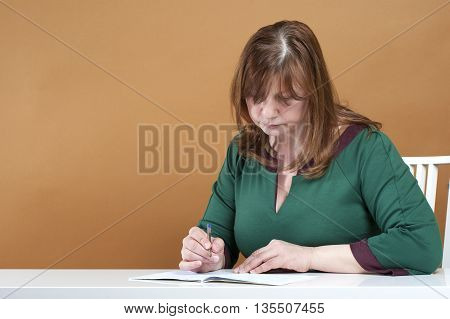 Middle-aged Woman Checks The Notebook..