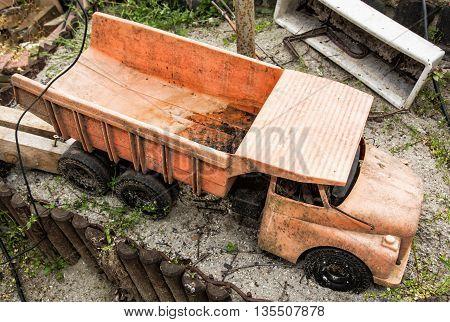 Dirty children truck at the garden. Outdoor toy. Retro toy. Leisure activity. Preschool game theme. Nobody scene.