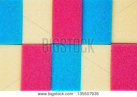 Colored kitchen sponges arranged in a row. Ware washing theme. Absorbent material. Abstract scene.