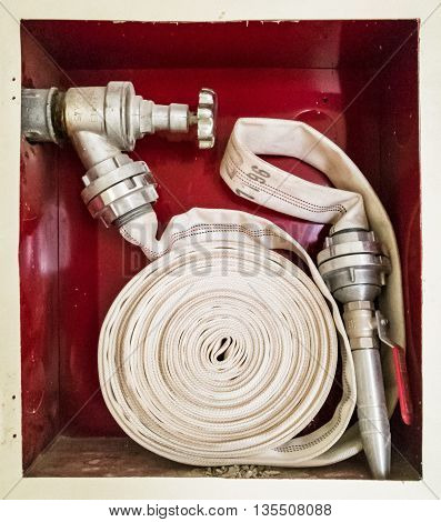 Fire with stacked hose. Water tap. Modern system. Iron hydrant valve. Socket for connection of fire hose.