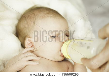 Baby Drinking From Bottle With Nipple In Mouth