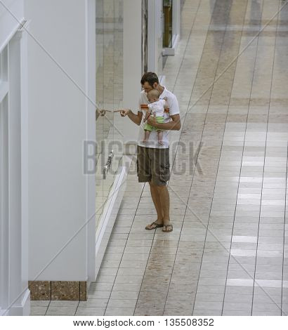 Family Shopping. Young Father And His Daughter In The Mall. He Shows Something