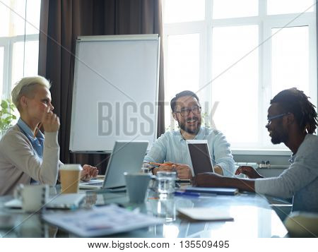 Smiling colleagues having meeting on strategy of business