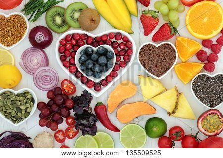 Paleo diet health and superfood of fruit, vegetables, nuts and seeds in heart shaped bowls on distressed white wood background, high in vitamins, antioxidants, dietary fiber and minerals.