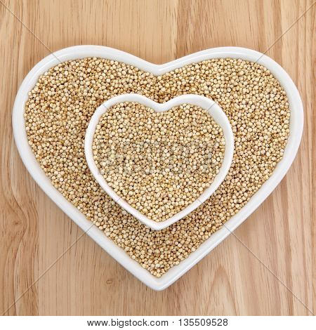Quinoa grain health food  in heart shaped porcelain dishes over beech wood background. Salvia hispanica.