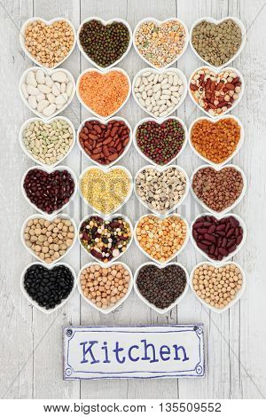 Vegetable pulses selection in heart shaped porcelain dishes with old metal kitchen sign over distressed white wooden background.