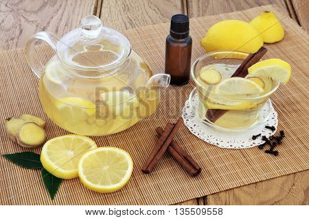 Cold and flu alternative medicine with hot lemon, honey and spice drink in a cup and glass teapot with fresh fruit and aromatherapy bottle on bamboo over oak background.