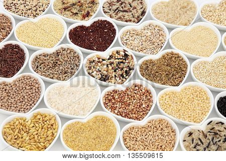 Grain health food selection in heart shaped porcelain china dishes over white background.