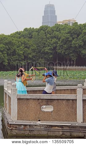 Wuhan, China - June 23, 2015: newlyweds are making interesting photos outdoor in Wuhan, China