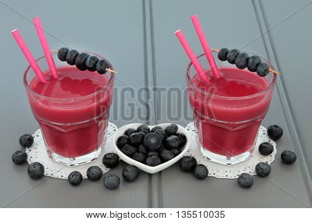 Blueberry smoothie health juice drink with fresh fruit on wooden grey background.
