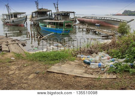 SANDAKAN, MALAYSIA - 23 JUNE 2016: Plastic pollution environmental problem. Bottles wash up on beach beside fishing village.