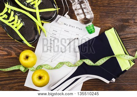 Sports items: sneakers headphones sports bra and measuring tape on the wooden background