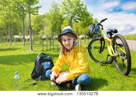 Teenage girl biker sitting on a green grass next to a mountain bike and and draws