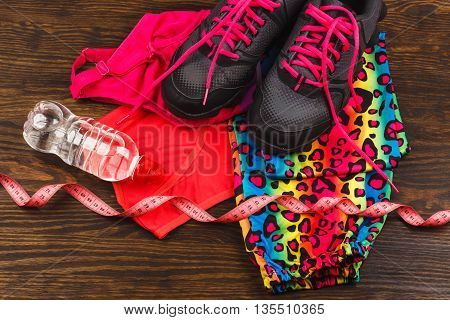 Sports items: measuring tape bottle of water and sport clothing on the wooden background