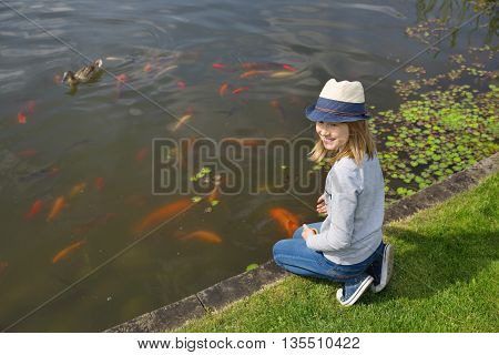 Happy girl teenager feeding fishes in a garden pond