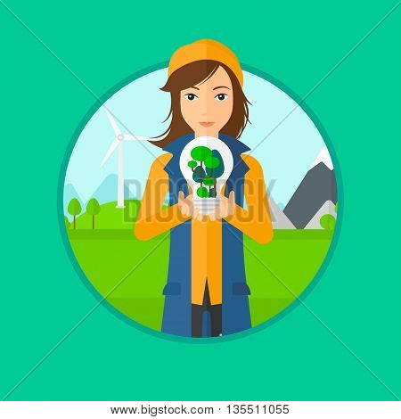 Woman holding light bulb with tree inside. Woman with light bulb and tree inside standing on a background with wind turbines. Vector flat design illustration in the circle isolated on background.