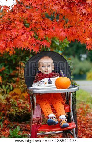 Halloween Holiday. Little Girl Sitting Next To A Pumpkin