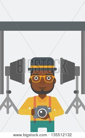 An african-american man holding a camera on the background of photo studio with lighting equipment vector flat design illustration. Vertical layout.
