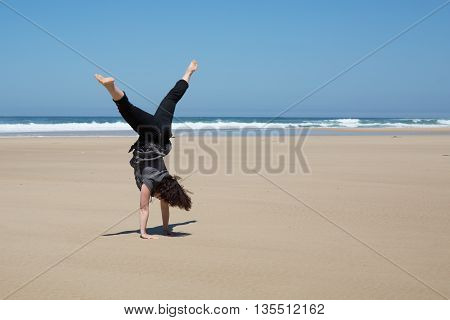 Woman Practicing Yoga Outdoors Over Blue Sky