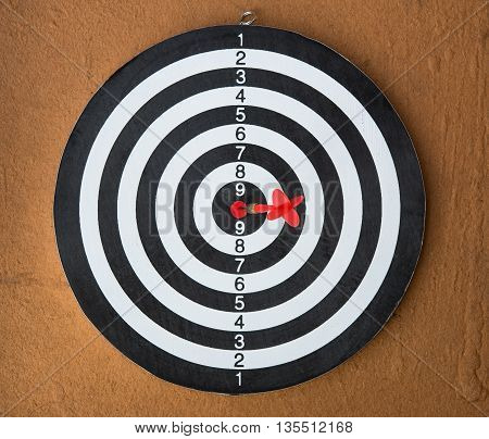dart board with darts arrow in the target center on wood background.(Success business concept)