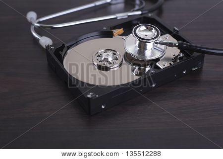 Depiction of computer repairs and digital data recovery with a stethoscope scanning for lost information on a hard drive disc.